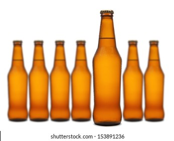 A beer bottle stands out from a group of seven.