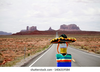 A beer bottle wearing a sombrero and poncho on a highway near Monument Valley, Utah.