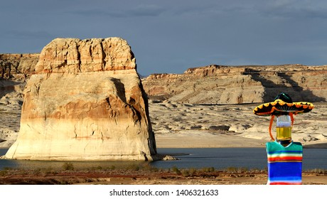 A beer bottle wearing a sombrero and poncho by Lake Powell, Utah.  It is in front of an area called Lone Rock.