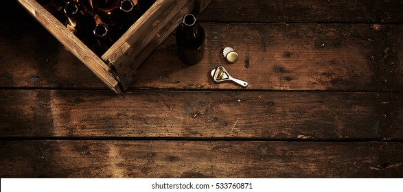 Beer bottles in a crate on an old weathered wooden counter in a rustic pub or tavern with an opener alongside and copy space, overhead view in horizontal banner format