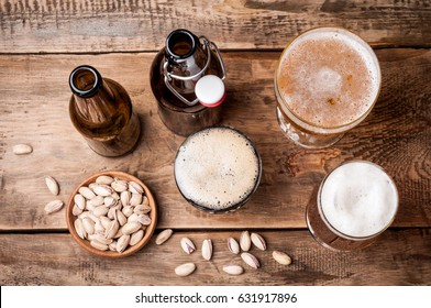 Beer in bottles and glasses on a wooden table. Beer and snacks pistachio nuts top view. Drink and snack for the football match or rest in pub