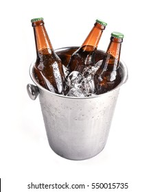 Beer bottles in ice bucket, isolated on white