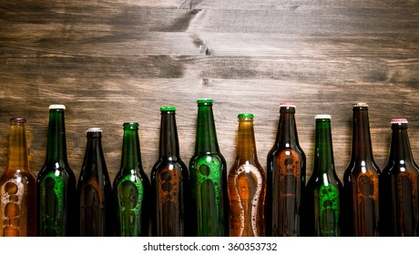 Beer bottles on a wooden table . Top view