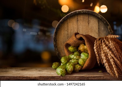 Beer brewing ingredients Hop in bag and wheat ears on wooden cracked old table. Beer brewery concept. Hop cones and wheat closeup. Sack of hops and sheaf of wheat on vintage background.