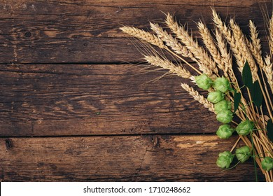 Beer brewing ingredients Hop and wheat ears on wooden cracked old table. Beer brewery concept. Hop cones and wheat closeup. Sack of hops and sheaf of wheat on vintage background. - Shutterstock ID 1710248662