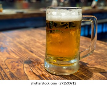 Beer with bubble level in glass on wooden table