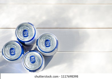 Beer cans on white wooden background. Copy space. Coolness beverage in the heat