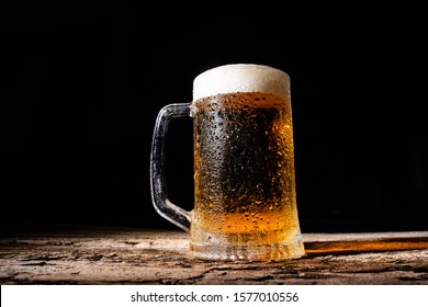 Beer. Cold Craft light Beer in a glass with water drops. Pint of Beer. Glass of beer with foam on dark wooden background.