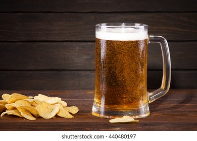 Beer. Cold beer in glass with chips on a dark background.