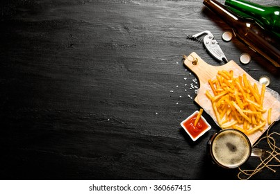 The beer concept. Beer and fries with tomato sauce on the chalkboard. Free space for text. Top view