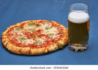 Beer and delicious freshly baked pizza, just out of the oven on a wooden board