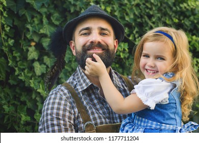 Beer Festival Oktoberfest.Man  in traditional bavarian clothes Lederhose with little girl on his hands in dirnndl. Papa and daughter