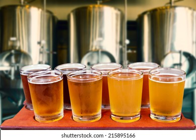 Beer flight of eight glasses of craft beer on a serving board with fermenting tanks background.