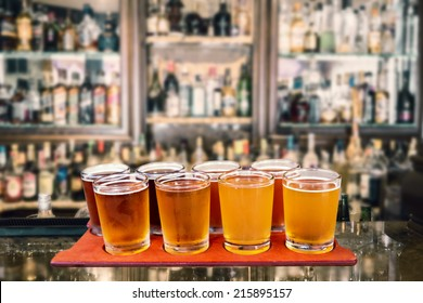 Beer flight of eight sampling glasses of craft beer on a serving board in a bar.