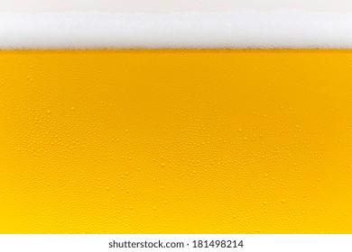 Beer foam crown with golden drops of condensation