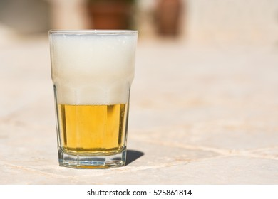 Beer with the foam in a glass on the ceramic tile
