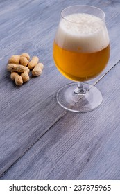 Beer with foam and peanuts on the side