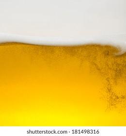 Beer foam wave on golden glass
