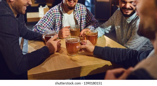 Beer friends free time concept. Cheerful friends with glasses and beer in the bar.