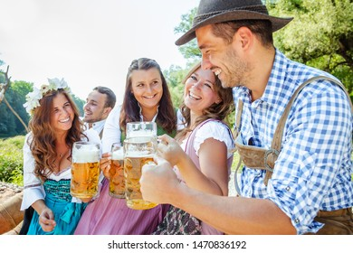 Beer garden in Bavaria, Germany - friends in Tracht, Dirndl and Lederhosen.Five friends having fun on Bavarian River and clinking glasses with beer.Oktoberfest