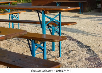 beer garden bench table and umbrella below big oak tree on a summer holiday evening before sunset in south germany