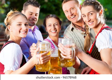 In Beer garden - friends in Lederhosen drinking a fresh beer in Bavaria, Germany