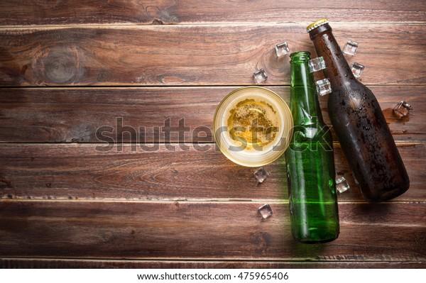 錆びた木の背景にビールガラスとボトル、テキスト用スペース、上面図