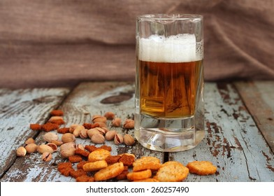 Beer in a glass, croutons and pistachios on a textural wooden table. Beer and beer snack.