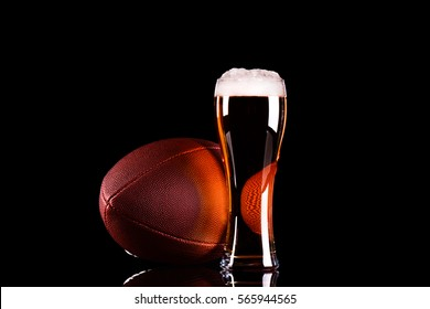Beer glass with foam and American football ball on black background