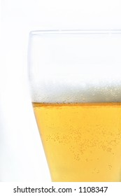 beer in glass with foam and bubbles isolated on white