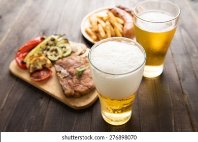 Beer in glass with gourmet steak and french fries on wooden background