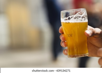 Beer in a glass in his hand, illuminated by sunlight