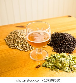 Beer in glass, with hops and malt displayed on table