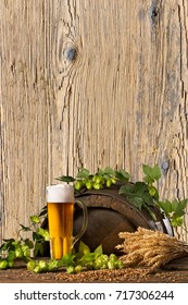 Beer Glass with Hops and Wheat on the Wooden Desk