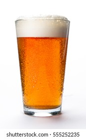 Beer glass with medium colored beer and foam on a white background