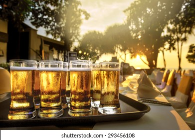 Beer in the glass on the blurred dinner table and sunset