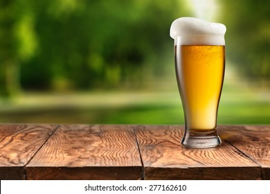 Beer in glass on wooden table with blurred city park on background, natural background with bokeh