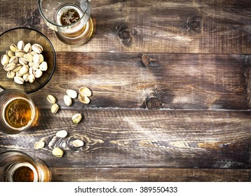 Beer, glass, pistachios on a wooden table. Beer background, top view