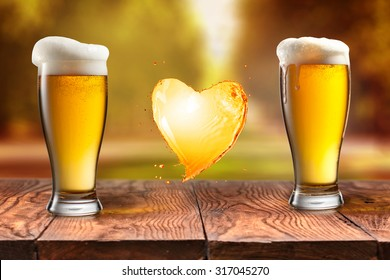 Beer in glass and splash in shape of heart on wooden table with blurred autumn city park on background, natural background with bokeh