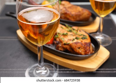 Beer glass and tasty steak, food background