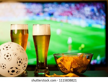 beer glasses and chips in front of tv - watching football at home