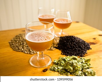Beer in glasses, hops and malt displayed on table