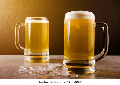 Beer in glasses on concrete table near granite background.