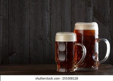 Beer glasses on table, dark wooden background with copy space