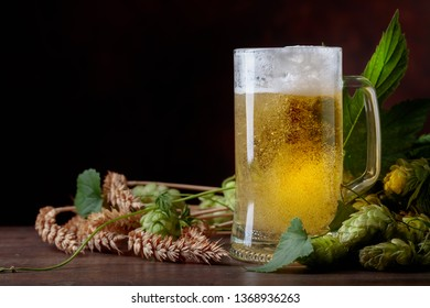 Beer, grain and hops on a old wooden table. Free space for your text.
