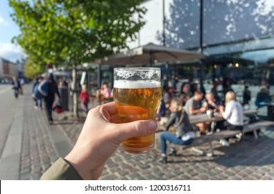 Beer in hand of visitor of street food market of Copenhagen, Denmark. Leisure in Scandinavia with drinks and food of popular city stores.