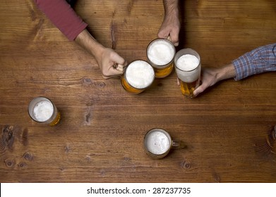 beer and hand at the wooden table