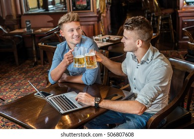 Beer and laptop. Two businessmen friends men drinking beer and having fun together in the bar and working on the laptop