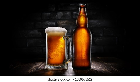 Beer in mug and bottle on a background of black brick wall