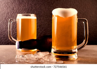 Beer in mug and Bottle on concrete table near granite background.